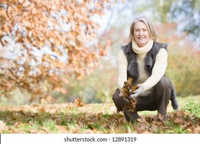 Senior woman collecting autumn leaves on walk