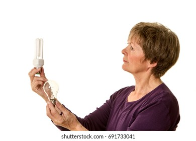 Senior woman comparing an old fashioned lightbulb to an eco-friendly one. Conceptual image for environment related ideas.