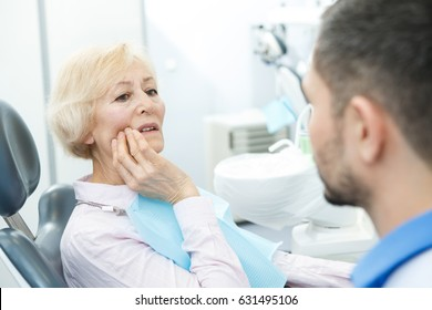 Senior woman complaining on toothache to her dentist at the clinic teeth dentistry dental examination checkup operation procedure treatment helping help experienced trust insurance aching painful