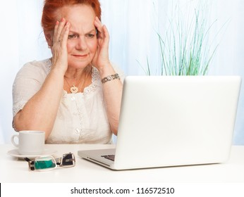 Senior woman with confused expression on her face sitting behind her laptop