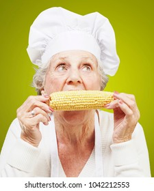 senior woman cook eating a corncob against a yellow background