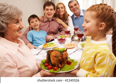 Senior woman with cooked turkey looking at her granddaughter and both smiling