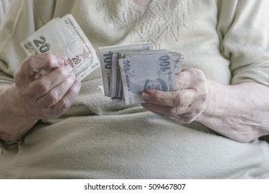 senior woman counting money (turkish lira)