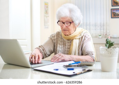Senior woman counting utility bills at her home.