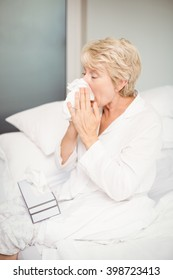 Senior woman covering nose while sneezing in bedroom at home