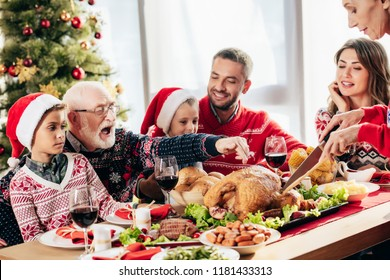 senior woman cutting turkey for christmas dinner with happy family at home