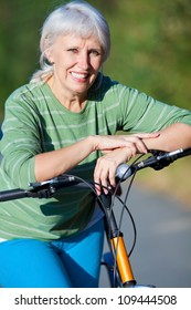 senior woman cycling in the summer park