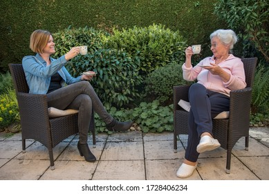 Senior woman and daughter with face masks having coffee with safety disctance