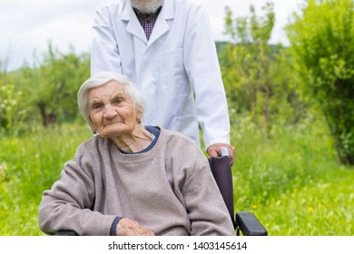 Senior woman with dementia sitting in a wheelchair outdoor, male doctor taking care of her - eldercare
