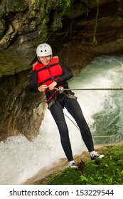 Senior Woman Descending Into A Waterfall Vertical Shot