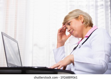 Senior woman doctor at the computer in her office holding her head. Fatigue. Stress. Work days.