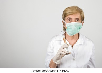 Senior woman doctor holding a syringe ,copy space for text message in left part of image