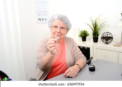 Senior woman in doctor's office showing hearing aid equipment