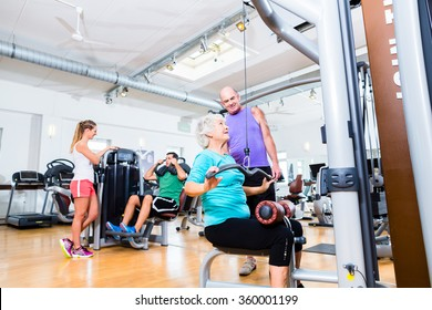Senior woman doing back training with trainer in gym at machine