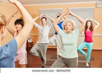 Senior woman doing balance exercise in yoga class at fitness studio