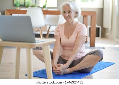 Senior woman doing fitness exercises from home- virtual classes