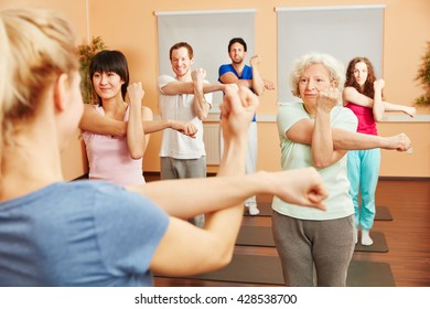 Senior woman doing pilates with a group of people at a fitness center