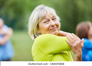Senior woman doing a stretching exercise for the upper arms in the gym class