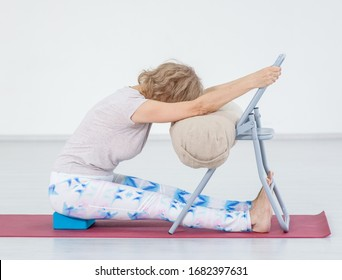 Senior woman doing yoga with chair in a gym. Stretching exercises