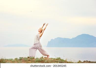 Senior woman doing yoga exercises with mountain on the background