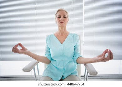 Senior woman doing yoga on chair at fitness studio