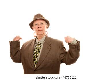 Senior woman in drag flexing her muscles in baggy jacket