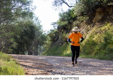 Senior woman dressed in sports clothes and a hat running down the mountain