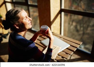 Senior woman with drink taking pleasure in solitude