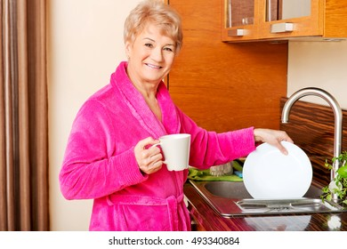 Senior woman drinking coffee in kitchen and washing plate