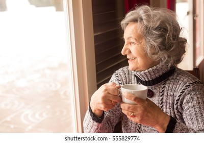 Senior woman drinking coffee and looking through window