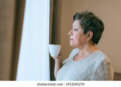 Senior woman drinking coffee near a window at home