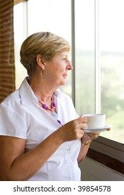 senior woman drinking coffee near a window at home
