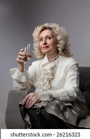 a senior woman drinking a glass of sparkling wine