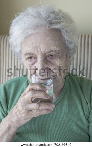 A senior woman drinking water