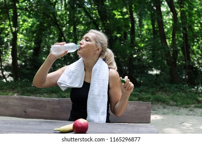 Senior woman drinking water and having sneack in park.