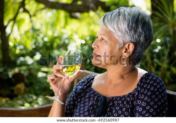 Senior woman drinking wine at the park