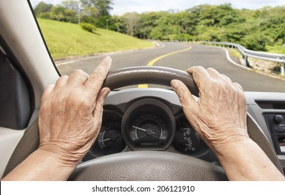 Senior woman driving a car slowly on highway