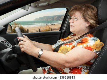 Senior Woman Driving a Car Through the Beach Road