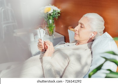 senior woman in earphones using smartphone while lying on hospital bed