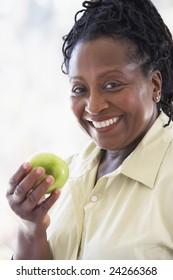 Senior Woman Eating Green Apple And Smiling At The Camera