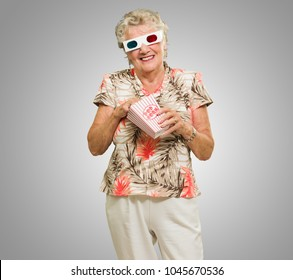 Senior Woman Eating Popcorn Watching 3d Movie On Grey Background