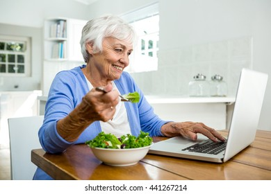 Senior woman eating salad while using laptop at table in kitchen