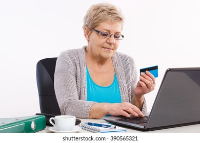 Senior woman, an elderly pensioner with credit card and laptop paying over internet for utility bills or online shopping, surfing internet, typing on computer keyboard