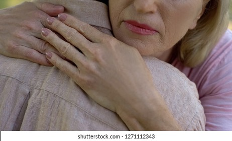 Senior woman embracing man after bad news about disease or loss, family support