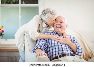 Senior woman embracing man in living room