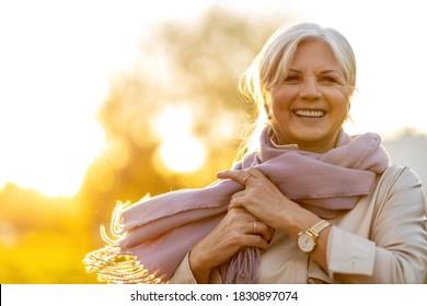 Seniorin, die bei Sonnenuntergang Herbstfarben genießt