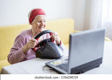 Senior woman enjoying car racing video game on laptop while sitting on couch at home