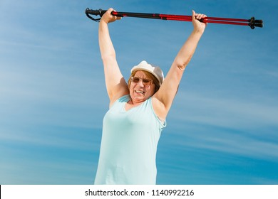 Senior woman enjoying nordic walking, doing warmup exercises with poles outdoor, sunny summer day. Health, activity in old age.