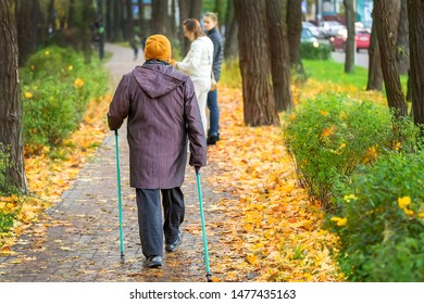 Senior woman enjoying nordic walking at beautiful colorful autumn park. Old age person doing pole walk excercise outdoors. Elderly people healthcare and fitness