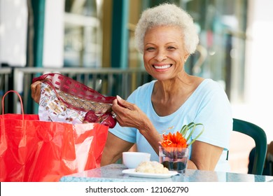 Senior Woman Enjoying Snack At Outdoor Cafe After Shopping